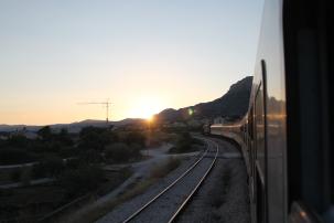 Trein baant zich een weg richting de zonsondergang en de bergen